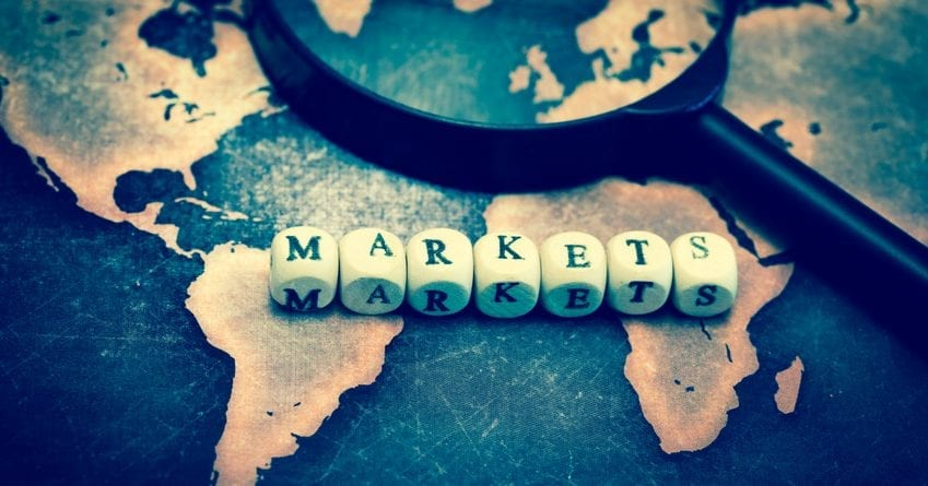 MARKETS with magnifying glass on grunge world map