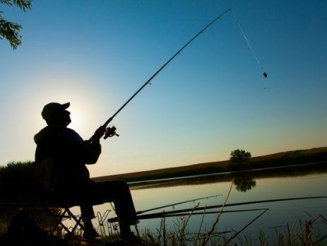 silhouette of man fishing on lake
