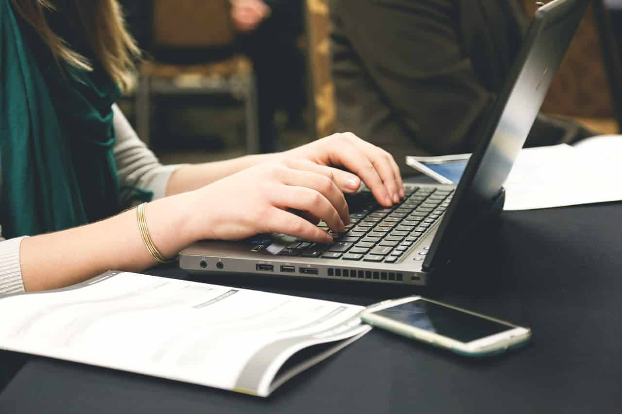 woman writing a blog post on her computer